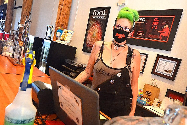 Both staff and customers wear masks at Puscifer the Store in Jerome, where Nichole Bonney greeted customers on the day they reopened last June.  Gov. Doug Ducey signed legislation Friday that will bar government officials from requiring businesses to enforce new mask mandates. VVN file photo/Vyto Starinskas