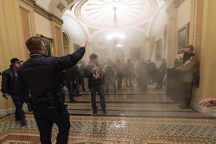 In this Jan. 6, 2021 photo, smoke fills the walkway outside the Senate Chamber as rioters loyal to President Donald Trump are confronted by U.S. Capitol Police officers inside the Capitol in Washington. New details from the deadly riot of Jan. 6 are contained in a previously undisclosed document prepared by the Pentagon. (Manuel Balce Ceneta/AP, File)