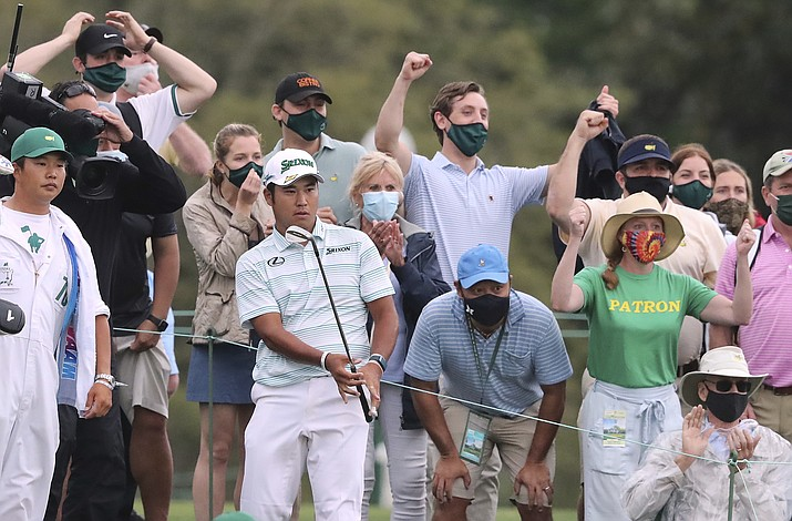 Spectators react as Hideki Matsuyama chips it close to the cup from the gallery to save par and finish in the lead at 11 under par during the third round of the Masters golf tournament at Augusta National, Saturday, April 10, 2021, in Augusta, Ga. (Curtis Compton/Atlanta Journal-Constitution via AP)