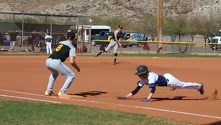Junior Kaden Hatchell of Kingman Academy dives safely back to first base during a pickoff attempt by Arizona Lutheran on Friday, April 9. (Photo by Casey Jones/Kingman Miner)