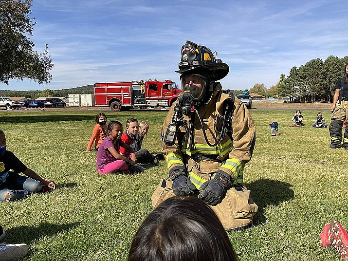 Williams Fire Captain Chase Pearson demonstrates how he puts on his fire gear for students during Fire Prevention Week. Williams Fire is hosting its 18th annual Fire Prevention Golf Tournament June 5. (Photo/Williams Unified School District)
