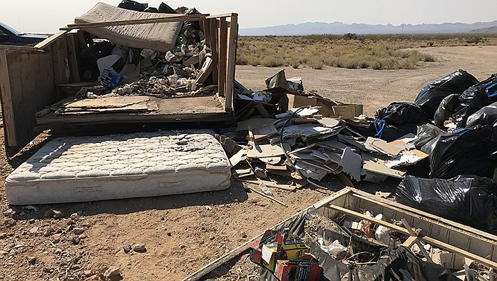 A Chloride man has been charged after allegedly dumping this pile of debris along Old Boulder Dam Highway near Chloride. (Mohave County courtesy photo)