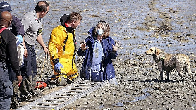 Camille Coelho, center, chats with Boston firefighter Josh Egan, kneeling, while stuck in deep mud along Boston Harbor while looking for sea glass at low tide, Thursday April 8, 2021 in Boston. (Stuart Cahill/The Boston Herald via AP)