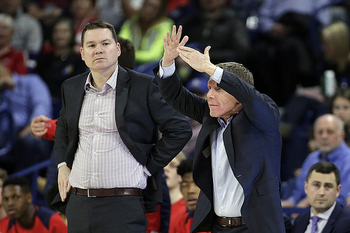In this Thursday, Feb. 1, 2018 file photo, Gonzaga head coach Mark Few, right, calls a timeout as assistant coach Tommy Lloyd looks on during the second half of an NCAA college basketball game against San Diego in Spokane, Wash. Arizona has hired longtime Gonzaga assistant Tommy Lloyd as its next men's basketball coach, Wednesday, April 14, 2021. The school says Lloyd will receive a five-year contract, pending approval by the Arizona Board of Regents. (Young Kwak, AP File)