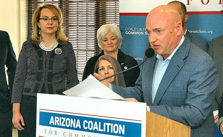 Former Arizona Rep. Gabrielle Giffords, far left, looks on as her husband and now U.S. senator, Mark Kelly, speaks at a 2017 event. Giffords recently was one of the speakers at a news conference in which she joined Democratic lawmakers who called on Congress to pass a background checks bill. (Capitol Media Services photo by Howard Fischer)