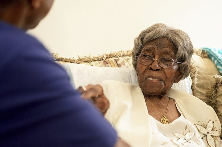 """This Aug. 13, 2016, file photo shows Roosevelt Patterson greeting his grandmother Hester """"Granny"""" Ford during Ford's 111th birthday party. Ford was either 115 or 116 years old depending on which census report was accurate. Either way, she was the oldest living American when she died Saturday, April 17, 2021, in Charlotte, according to the Gerontology Research Group, which tracks """"supercentenarians."""" They listed her age as 115 years and 245 days. (Diedra Laird/The Charlotte Observer via AP, File)"""