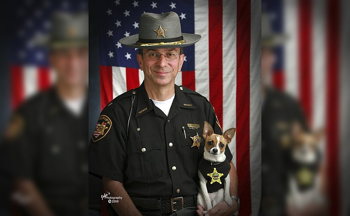 This 2006 image shows then Sheriff Dan McClelland and his small police dog Midge at the Geauga County, Ohio, sheriff's department. Both died on Wednesday, April 14, 2021. McClelland after a lengthy battle with cancer and Midge, perhaps, of a broken heart. The family said they will be buried together. McClelland retired in 2016, after 13 years as sheriff, and 44 total in the department. The last ten with Midge, a drug-sniffing Chihuahua-rat terrier mix certified by Guinness World Records as the smallest police dog on the globe. (John Hoffart via AP)