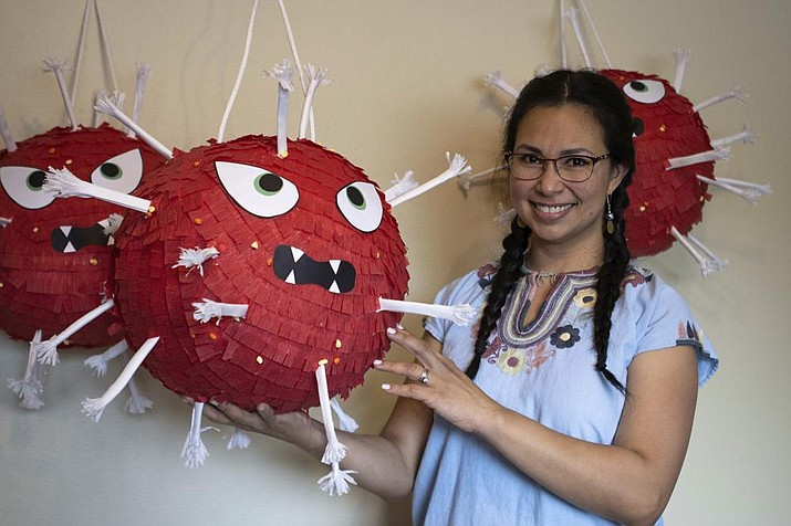 In this photo provided by Alaska Public Media, Carolina Tolladay Vidal displays custom COVID-19 piñatas in her home in Anchorage, Alaska, on April 14, 2021. After her business ground to almost a ha...