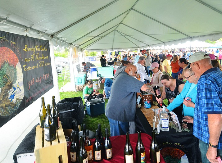 Mitch Levy of Burning Tree Cellars pours wine for a visitor at last weekend's 20th annual Camp Verde Pecan & Wine Festival. Levy and his helpers represented one of eight local wineries at the event. VVN/Vyto Starinskas photo