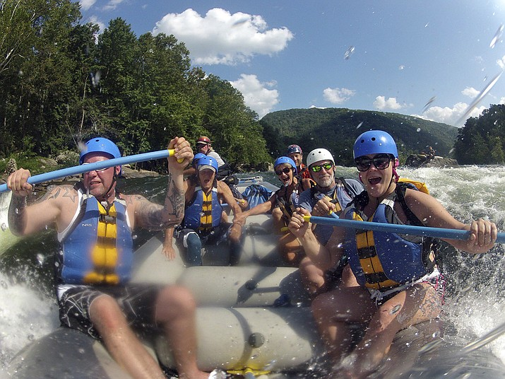 Whitewater rafters are shown rafting the lower New River Gorge, near Fayetteville, W.Va. A program launched Monday, April 12, 2021, will try to lure outdoor enthusiasts to live and work in West Virginia with enticements of $12,000 cash and free passes for a year for recreation destinations such as whitewater rafting and golf. (Lawrence Pierce/Charleston Gazette-Mail via AP, File)