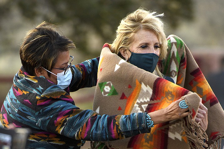 Navajo Nation Council Member Eugenia Charles Newton helps first lady Jill Biden cover up with a Navajo Pendleton blanket during a live radio address to the Navajo Nation at the Window Rock Navajo Tribal Park & Veterans Memorial in Window Rock, Arizona on April 22, 2021.(Mandel Ngan/Pool via AP)