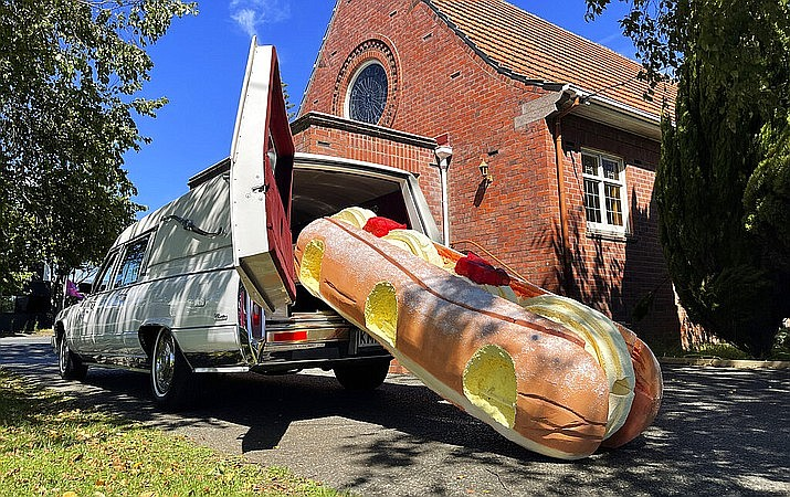 This photo provided by Ross Hall, shows a cream doughnut-shaped coffin for the funeral of Phil McLean outside a church in Tauranga, New Zealand on Feb 17, 2021. Auckland company Dying Art makes unique custom caskets which reflect the people who will eventually lay inside them, whether it's a love for fire engines, a cream doughnut or Lego. (Ross Hall via AP)