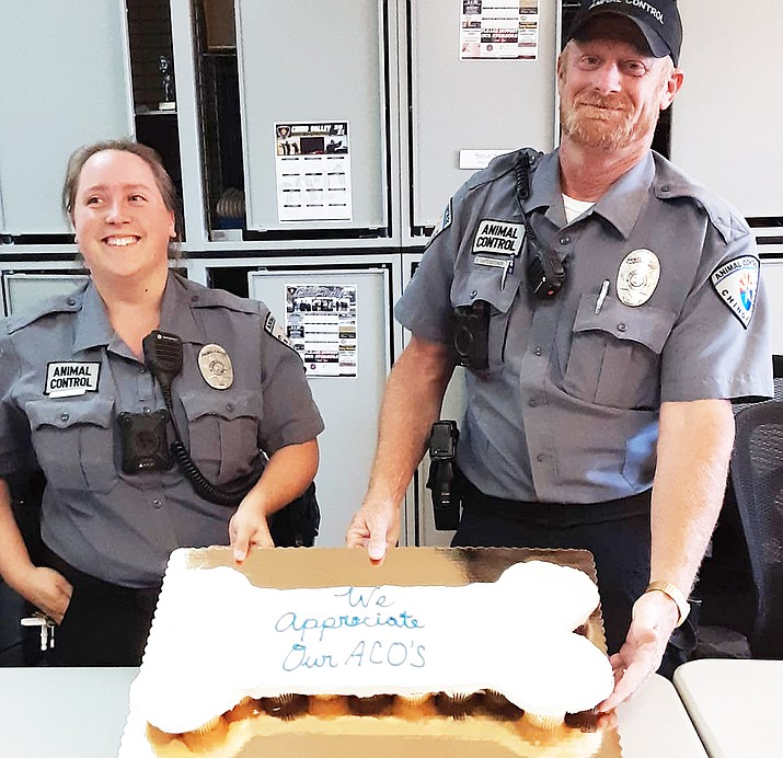 The Chino Valley Police Department took time last week to recognize and honor animal control officers Mary Forsmann, right, and Scott Unterseher by giving them a cake in the shape of a  bone for all their hard work. (CVPD, Facebook/Courtesy)