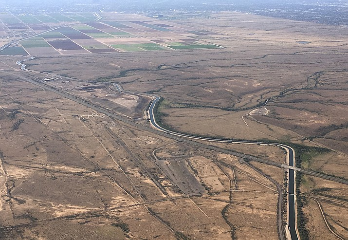 In this Oct. 8, 2019 image, the Central Arizona Project canal, which originates at the south end of Lake Havasu, runs east through rural desert near Phoenix. Arizona water officials say they are prepared to lose about one-fifth of the water the state gets from the Colorado River in what could be the first federally declared shortage in the river that supplies millions of people in the U.S. West and Mexico. (Ross D. Franklin/AP, File)