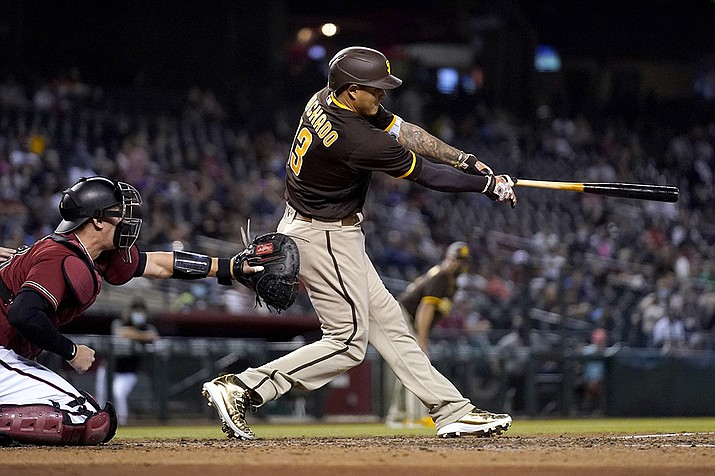 San Diego Padres' Manny Machado swings on a three-run triple next to Arizona Diamondbacks catcher Carson Kelly during the fifth inning of a baseball game Wednesday, April 28, 2021, in Phoenix. (Ross D. Franklin/AP)