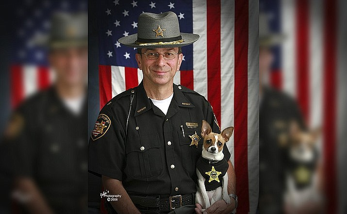 This 2006 image shows then Sheriff Dan McClelland and his small police dog Midge at the Geauga County, Ohio, sheriff's department. Both died on Wednesday, April 14, 2021. McClelland after a lengthy battle with cancer and Midge, perhaps, of a broken heart. The family said they will be buried together. (John Hoffart via AP)