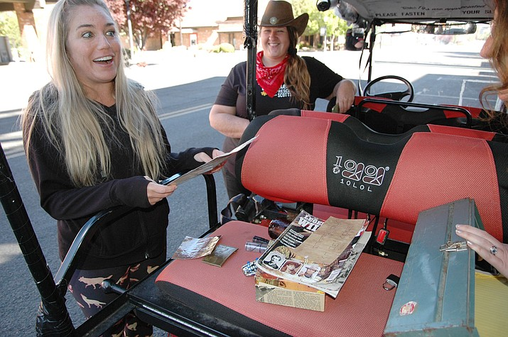 Holly Morgan, left, looks over materials that she has unlocked for clues to begin Prescott Puzzle Rides' Wild West Heist ride on Thursday, April 29, 2021, on Granite Street in downtown Prescott. Looking on are head puzzle master Shawna Rodriguez, middle, and Prescott Puzzle Rides founder Katie Dufort, right. (Doug Cook/Courier)