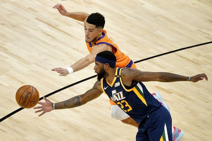 Phoenix Suns guard Devin Booker and Utah Jazz forward Royce O'Neale (23) battle for the ball during the first half of an NBA basketball game, Friday, April 30, 2021, in Phoenix. (Matt York/AP)