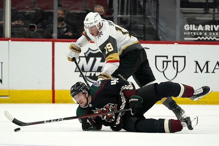 Vegas Golden Knights right wing Reilly Smith (19) sends Arizona Coyotes defenseman Ilya Lyubushkin (46) to the ice during the first period of an NHL hockey game Friday, April 30, 2021, in Glendale, Ariz. (Ross D. Franklin/AP)