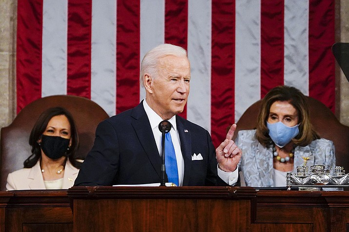 In this April 28, 2021 photo, President Joe Biden addresses a joint session of Congress in the House Chamber at the U.S. Capitol in Washington, as Vice President Kamala Harris, left, and House Speaker Nancy Pelosi of California look on. Biden has moved into a new phase of his presidency, having already begun to face a historic series of crises and largely dedicating his first 100 days to steady a nation reeling from the COVID-19 pandemic that has killed nearly 570,000 Americans and devastated its economy. (Melina Mara/The Washington Post via AP, Pool)