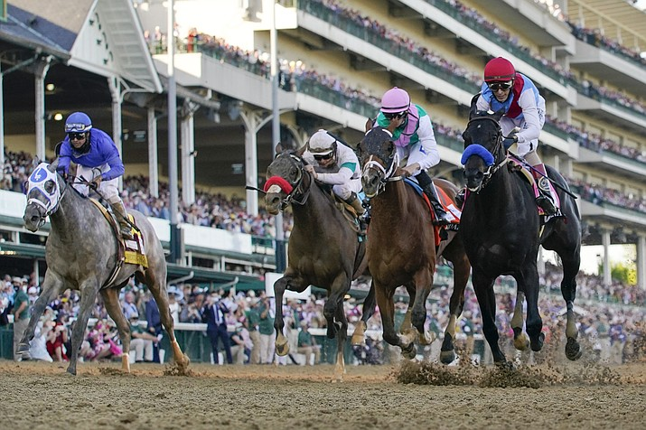 John Velazquez riding Medina Spirit, right, leads Florent Geroux on Mandaloun, Flavien Prat riding Hot Rod Charlie and Luis Saez on Essential Quality to win the 147th running of the Kentucky Derby at Churchill Downs, Saturday, May 1, 2021, in Louisville, Ky. (Jeff Roberson/AP)
