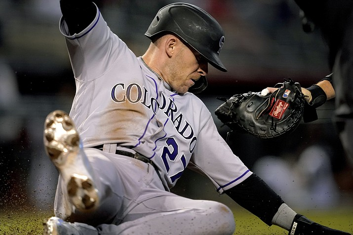 Colorado Rockies' Trevor Story (27) slides safely around the glove of Arizona Diamondbacks catcher Carson Kelly on a base hit by Ryan McMahon during the first inning of a baseball game, Saturday, May 1, 2021, in Phoenix. (Matt York/AP)
