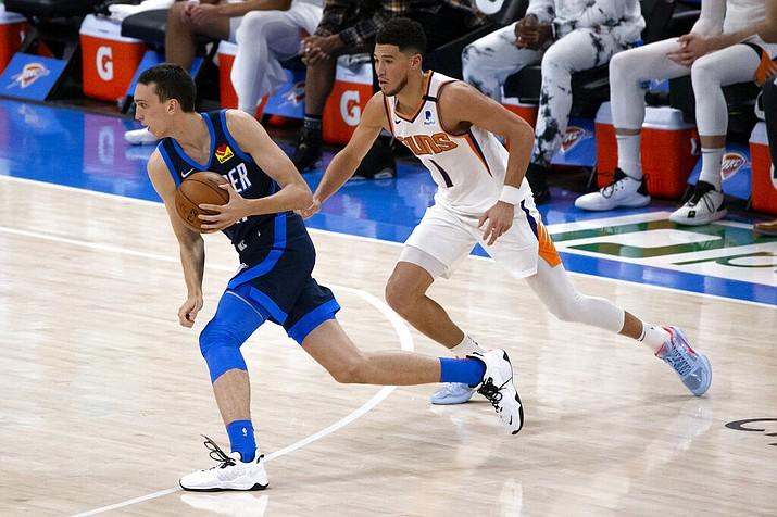 Oklahoma City Thunder forward Aleksej Pokusevski (17) goes against Phoenix Suns guard Devin Booker (1) during the first half of an NBA basketball game, Sunday, May 2, 2021, in Oklahoma City. (AP Photo/Garett Fisbeck)