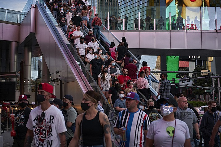 People ride an escalator along the Las Vegas Strip, Saturday, April 24, 2021, in Las Vegas. Las Vegas is bustling again after casino capacity limits were raised Saturday, May 1, to 80% and person-to-person distancing dropped to 3 feet (0.9 meters). (John Locher/AP)