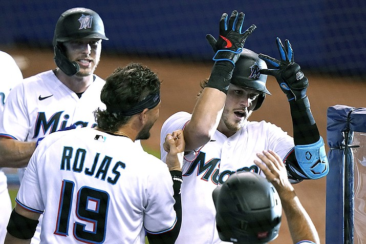 Miami Marlins' Brian Anderson (15) celebrates with Miguel Rojas (19) after hitting a three-run home run during the first inning of a baseball game against the Arizona Diamondbacks, Tuesday, May 4, 2021, in Miami. (Lynne Sladky/AP)