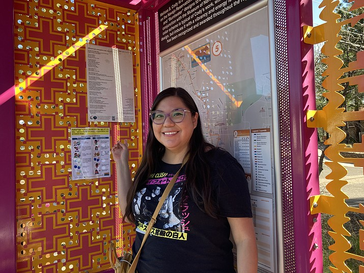 Amber McCrary points to poetry hanging up at the Museum of Northern Arizona's bus stop. The bus stop was designed by Melissa S. Cody, a Diné weaver.(Katherine Locke/NHO)