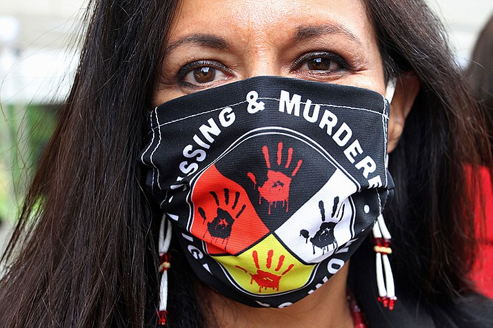 Jeannie Hovland, the deputy assistant secretary for Native American Affairs for the U.S. Department of Health and Human Services, poses with a Missing and Murdered Indigenous Women mask, in Anchorage, Alaska, Aug. 26, 2020, while attending the opening of a Lady Justice Task Force cold case office in Anchorage, which will investigate missing and murdered Indigenous women. From the nation's capitol to Indigenous communities across the American Southwest, top government officials, family members and advocates are gathering Wednesday, May 5, 2021, as part of a call to action to address the ongoing problem of violence against Indigenous women and children. (AP Photo/Mark Thiessen, File)