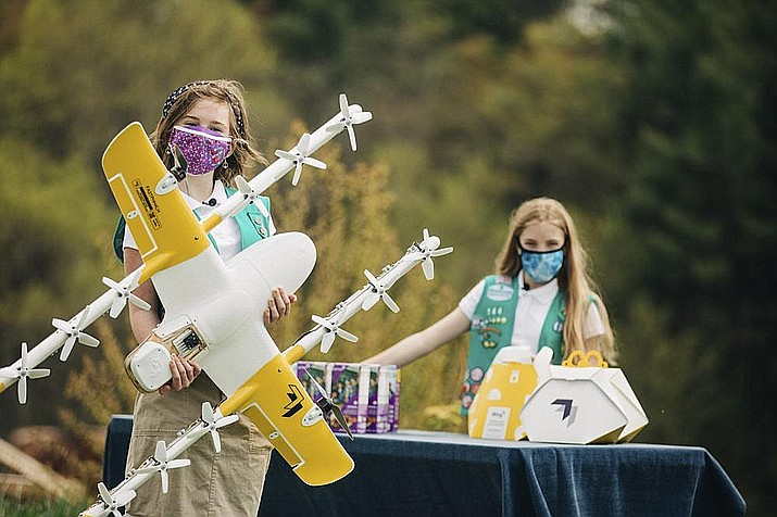 Girl Scouts Alice, right, and Gracie pose with a Wing delivery drone in Christiansburg, Va. The company is testing drone delivery of Girl Scout cookies in the area. (Sam Dean/ Wing LLC via AP)
