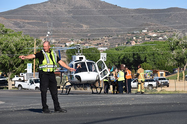 A police officer directs traffic Thursday, May 6, 2021, at the intersection of highways 69 and 169 while a victim of a four-vehicle crash is loaded into a helicopter for transport to a hospital. (Richard Haddad/Tribune)