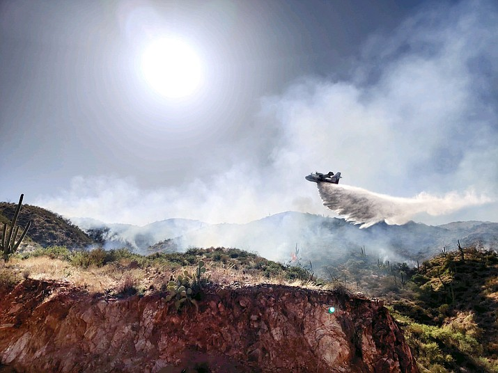 """Pictured is the """"Super Scooper"""" — a one-of-a-kind aircraft — dropping a load of water on the Tussock Fire burning southwest of Crown King, Arizona. The plane is using water from nearby Lake Pleasant. (Southwest Area Type 1 Incident Management Team/Courtesy)"""