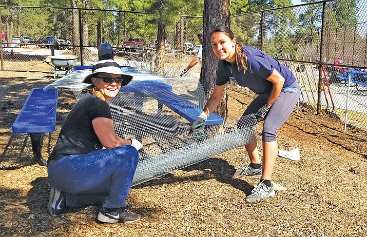 Mayor Clarinda Vail and TFD Business Administrator and firefighter Kate Maragos trim wire lining to keep voles and other pests from entering the flower beds from below. (Lo Frisby/WGCN)