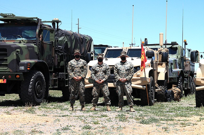 U.S. Marines from the 2nd Marine Logistics Group, 2nd Transportation Battalion stationed in Camp Lejeune, North Carolina stand in front of their convoy traveling to Twenty-Nine Palms, California. (Loretta McKenney/WGCN)