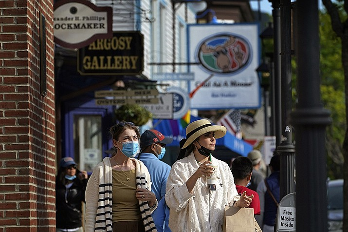 Visitors walk on a busy sidewalk, Saturday, May 15, 2021, in Bar Harbor, Maine. Gov. Janet Mills is eliminating most outdoor distancing requirements imposed during the COVID-19 pandemic as the tourism season begins to kick into gear. (Robert F. Bukaty/AP)