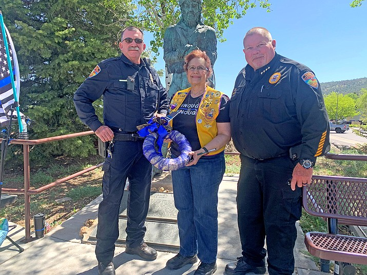 Patty Williams with the Williams Lions Club presents a wreath to Williams Police Chief Herman Nixon (right) and detective Jerry Wilson at Monument Park. Williams Volunteer Fire Department and community members gathered to honor fallen officers and the Williams Police Department during a ceremony for Police Memorial Day May 14. (Loretta McKenney/WGCN)