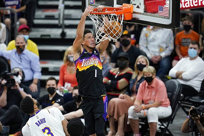 Phoenix Suns guard Devin Booker (1) dunks as he drives past Los Angeles Lakers forward Anthony Davis (3) during the first half of Game 1 of their NBA basketball first-round playoff series Sunday, May 23, 2021, in Phoenix. (AP Photo/Ross D. Franklin)