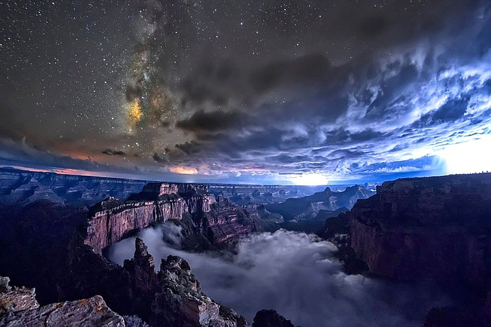 The Milky Way Galaxy fills the night sky above a telescope viewing area illuminated by red lights on the South Rim of Grand Canyon National Park. (Photo/NPS)