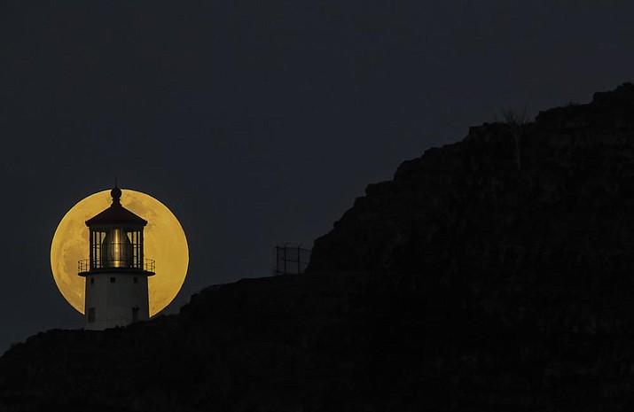 The moon rises behind the Makapuu lighthouse on Tuesday, May 25, 2021, in east Honolulu, before a lunar eclipse. (Jamm Aquino/Honolulu Star-Advertiser via AP)