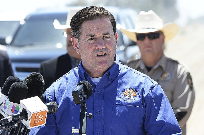 Arizona Gov. Doug Ducey addresses the media at the U.S-Mexico border in Yuma, Ariz, April 21, 2021. A budget deal struck between Republican leaders of the Arizona Legislature and Ducey includes implementing a flat 2.5% income tax that cuts $1.5 billion a year from state revenue and keeps higher earning taxpayers from having to directly pay a new 3.5% surcharge to fund schools. (Randy Hoeft/The Yuma Sun via AP, File)