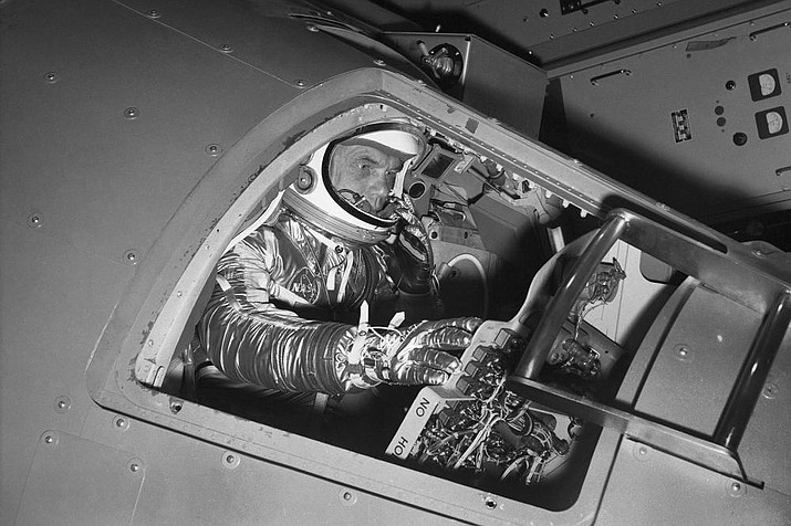 In this Jan. 11, 1961 file photo, Marine Lt. Col. John Glenn reaches for controls inside a Mercury capsule procedures trainer as he shows how the first U.S. astronaut will ride through space during a demonstration at the National Aeronautics and Space Administration Research Center in Langley Field, Va. In 2021, as more companies start selling tickets to space and the cosmos opens for travel like never before, a question looms above all others. Who gets to call themselves an astronaut? (AP Photo/File)