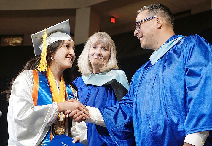 Chino Valley High School co-valedictorian Maria Acosta, left, shakes hands with Assistant Principal Marty Campitelli, right, and Principal Heidi Wolf after walking across stage to receive her diploma Wednesday, May 26, 2021, at the Findlay Toyota Center in Prescott Valley. (Aaron Valdez/Courier)