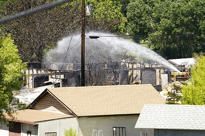 Fire crews work on a charred home from the Spur Fire Friday, May 28, 2021, that torched 150 acres and destroyed several homes and other structures in Bagdad, Arizona. (Rob Schumacher/The Arizona Republic via AP, Pool)