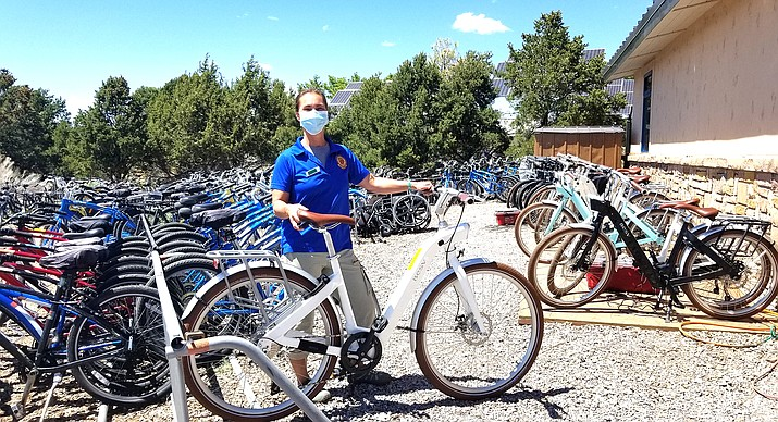 """Jenn Kidd, Bright Angel Bikes bicycle manager, shows off a new """"European style"""" e-bike. (Lo Frisby/WGCN)"""