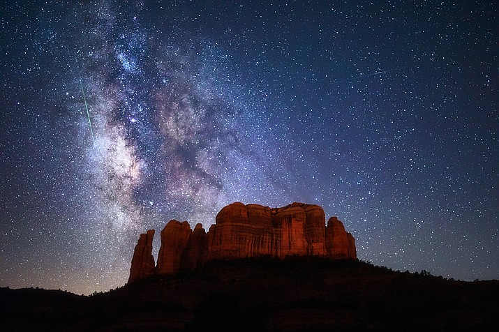 A meteor streaks through the Milky Way above Cathedral Rock in Arizona.(Adobe stock)