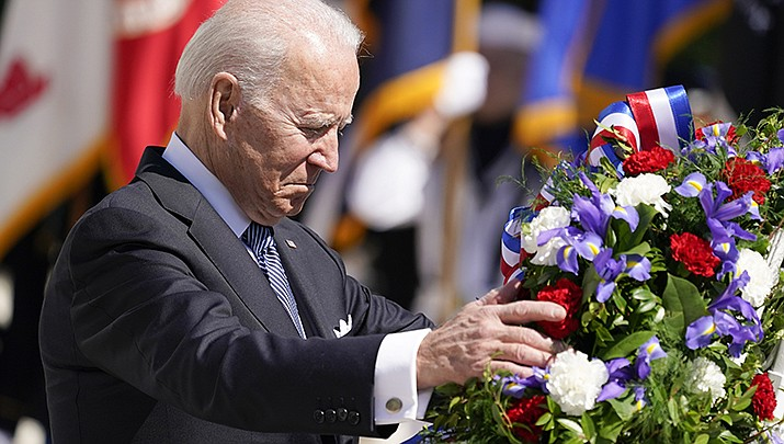 President Joe Biden adjusts a wreath at the Tomb of the Unknown Soldier at Arlington National Cemetery on Memorial Day, Monday, May 31 in Arlington, VA. (AP Photo/Alex Brandon)