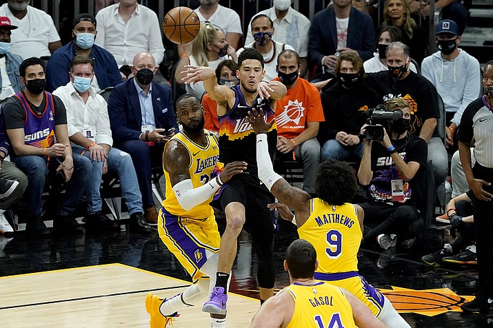 Phoenix Suns guard Devin Booker passes over Los Angeles Lakers forward LeBron James, left, and guard Wesley Matthews (9) during the first half of Game 5 of an NBA basketball first-round playoff series, Tuesday, June 1, 2021, in Phoenix. (Matt York/AP)