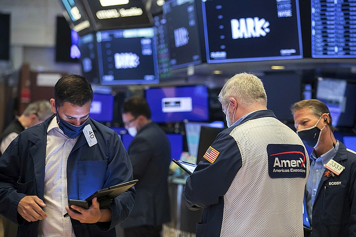 In this photo provided by the New York Stock Exchange, Craig Spector, left, works with fellow traders on the floor, Wednesday, June 2, 2021, in New York. Stocks edged higher Wednesday as gains in technology companies offset losses in industrial companies and other sectors. Investors are turning their attention to this month's jobs data, which will be out on Friday. (Courtney Crow/New York Stock Exchange via AP)
